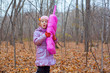 A little girl playing with a pink phone in autumn forest