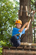 boy with equipment climber ready to go down from tree.