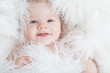 Portrait of a smiling baby wrapped in a white fur.