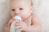 Closeup portrait of a baby with a bottle.