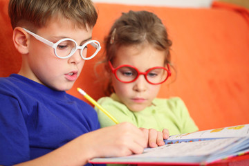 Girl and boy intently doing homework, focus on hinge glasses.