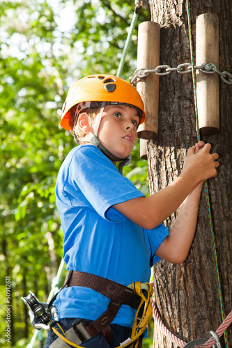 young man with climber equipment intently keeps rope