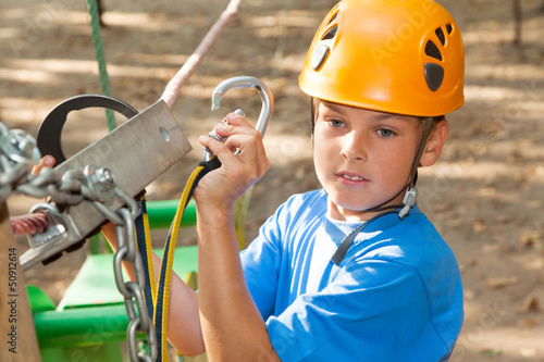 Young guy with equipment climber engages the anchor.