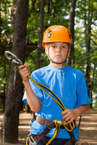 Young guy with equipment climber holding anchor.