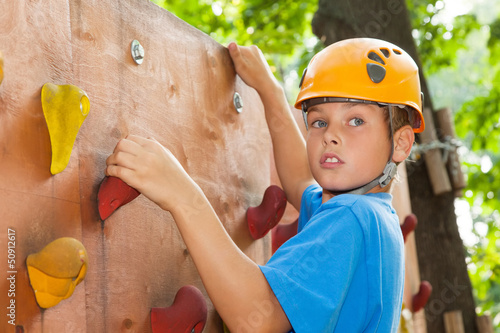 Young guy with climbed equipment on top of climbing wall.