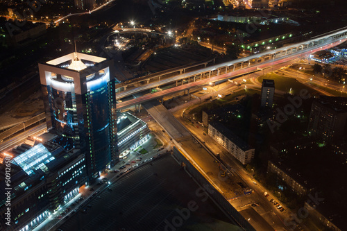 Night cityscape with high luminous buildings, bridges and road.