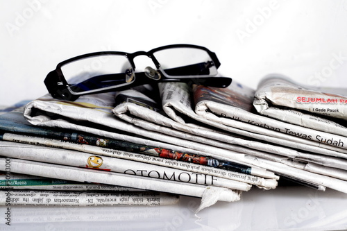 newspapers and eyeglass with reflection