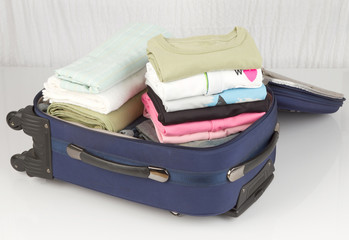 An opened suitcase packed with a lot of colorful cloths