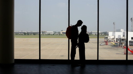 silhouette of pair of lovers near the window in airport