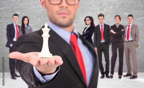 leader of a businessteam holding the white king of chess