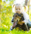 Happy child playing with dog in green field