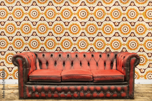 Retro styled image of an old sofa against a vintage wallpaper