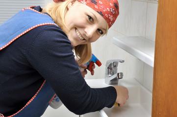 Junge Frau putzt Badezimmer