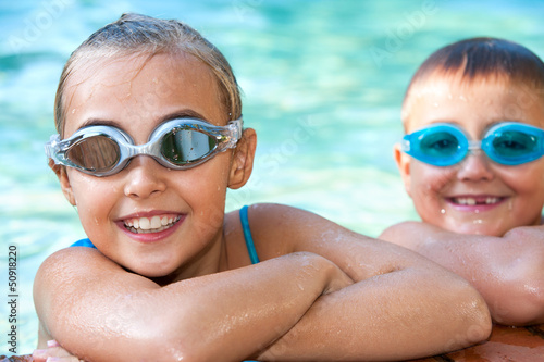 Kids in swimming pool with goggles.
