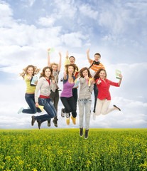 Group of teenagers jumping together on a green background