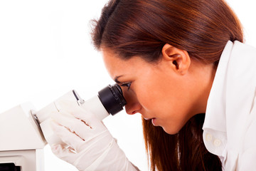 Closeup of a young female researcher looking into a microscope,