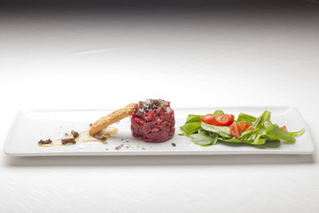 Elegant Seasoned beef tartare with black truffles. Gourmet Delic