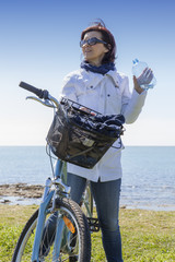 Mid aged healthy woman with water bottle on mountain bike