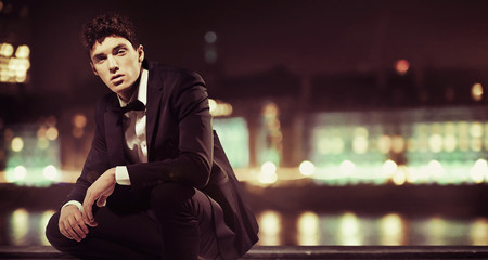 Stylish man with night town over the background