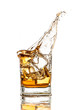 Whiskey glass with splash, isolated on white background