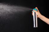 Sprayed air freshener in hand on grey background