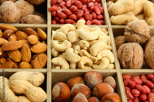 assortment of tasty nuts in  wooden box, close up