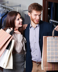 Pretty couple show their packets with gifts after shopping