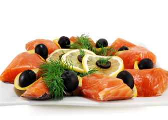 pieces of salmon with olives and lemon on a plate