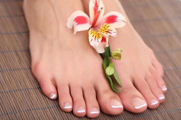Beautiful woman legs with pedicure on bamboo mat