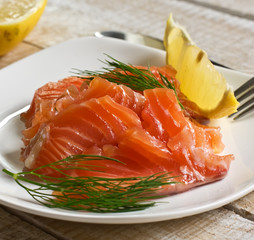 Salmon on plate with lemon on wooden background