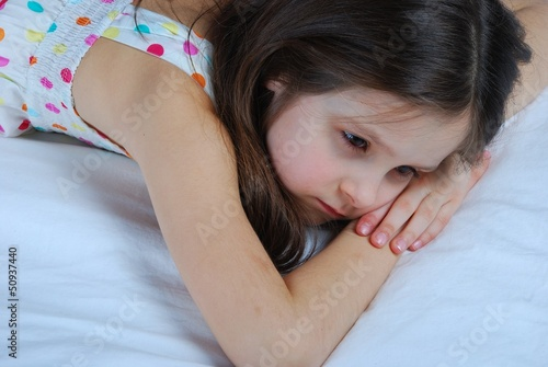 Young child, lying awake in his bed