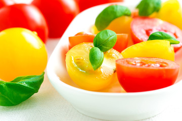 Assorted colorful red and yellow cherry tomatoes in plate on tab