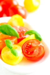 Assorted colorful red and yellow cherry tomatoes in plate on whi