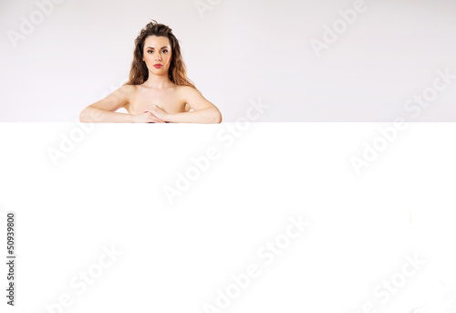 Naked brunette lady behind the board