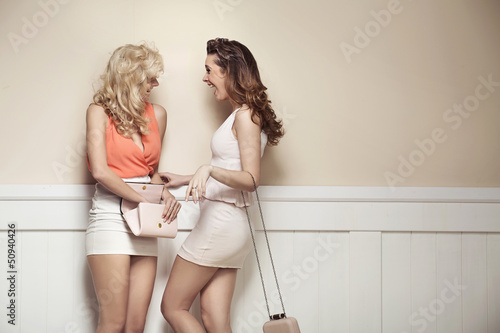 Laughing alluring girlfriends with sexy legs