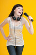 Expressive woman singing with a microphone, yellow background