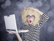 Portrait of funny girl in blonde wig with laptop. Studio shot.