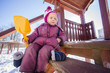 Adorable girl sit on stairs on wooden slide for kids on playgrou