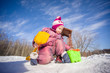 Adorable girl with shovel and pail dig snow on playground