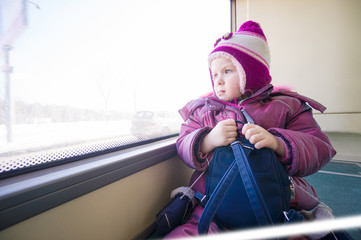 Adorable girl in winter clothes ride city bus and look to window