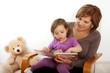 Eine Oma liest ihrer Enkeltochter aus einem Buch vor.