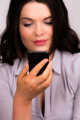 Beautiful young female reading iphone device