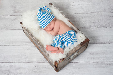 Sleeping Newborn Baby Wearing Pajamas and a Sleeping Cap