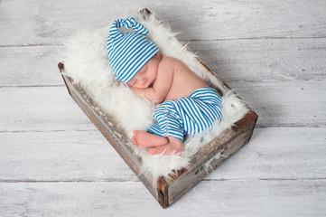 Sleeping Newborn Baby Wearing Pajamas and a Sleeping Cap