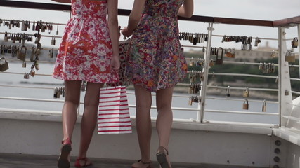 Girlfriends with shopping bags on the bridge, super slow motion