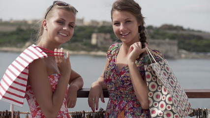 Happy female friends with shopping bags, super slow motion