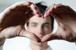 Mann formt Herz mit den Händen