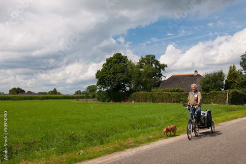 Elderly man at the bike with dog
