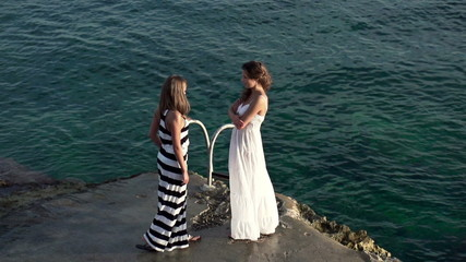 Girlfriends standing by the water, super slow motion