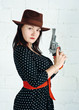 Woman in brown hat with gun